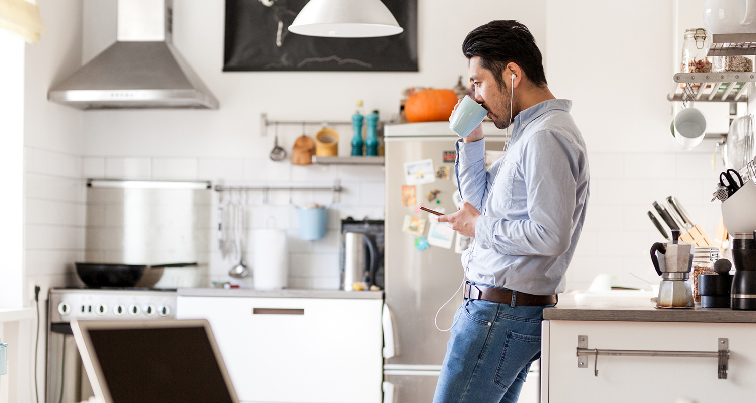 Man drinking coffee in kitchen